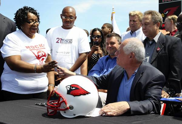 """Gov. Pat Quinn hands over the pen with which he signed the """"Rocky's Law"""" bill, to Annette Clark, Rocky's mom, during a ceremony at Eisenhower High School, in Blue Island, Ill. The new law requires school districts to provide catastrophic accident insurance for injured students."""
