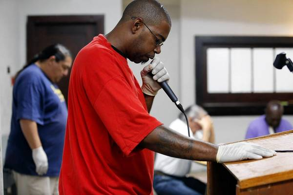 Derek Brooks, 43, friend of Juan Chavez, offers prayer before breakfast at First Friends Church in Long Beach. Chavez, who was shot and killed over two weeks ago by LAPD, used to preach at a Spanish bible study for the homeless.