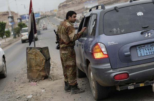 A Yemeni soldier inspects a car at a checkpoint on a street leading to the U.S. Embassy in Sana, Yemen.
