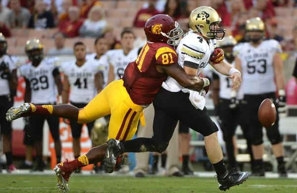 USC's Kevin Greene forces Colorado quarterback Jordan Webb to fumble the ball during a game at the Los Angeles Memorial Coliseum.