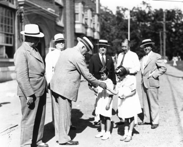 Gen. Harry C. Trexler hands out hot dogs to two Romper Day participants at the Allentown Fairgrounds on Aug. 29, 1933.