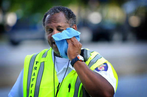 Baltimore's traffic officer Bobby Brown tries to stay cool in 95-degree heat while directing the afternoon rush hour at Light and Conway streets.