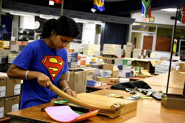 District 207 graduate Sariga Mathews, 18, cuts art kit vouchers in advance of student textbook sales. District officials hope the implementation of Google Chromebooks will reduce the number of textbooks students must purchase and carry around school.