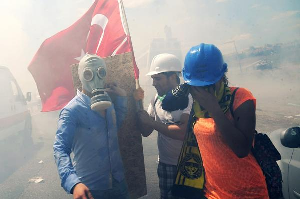 Demonstrators take cover from tear gas during clashes against Turkish police forces near a courthouse in Silivri, near Istanbul, on Monday, after a court decision to sentence a former army chief and other top brass to life in prison in a high-profile trial of 275 people accused of plotting to overthrow the Islamic-rooted government.