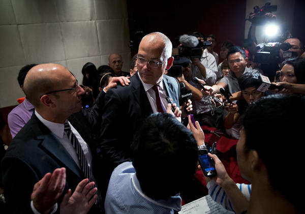 Theo Spierings, center, chief executive of New Zealand dairy giant Fonterra, is surrounded by journalists at a news conference in Beijing where he apologized for a tainted-milk scare.