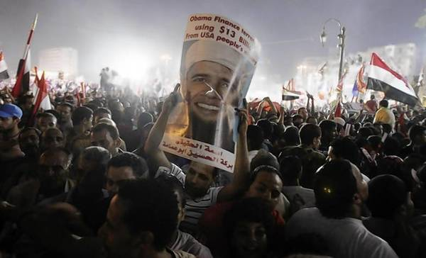 Anti-Mursi protesters cheer and hold up a poster depicting President Barack Obama with a beard at Tahrir square, where protesters gathered for a mass protest to support the army.