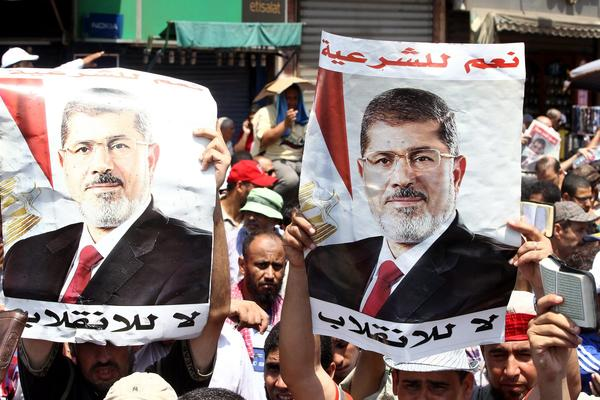 Supporters of Egypt's Muslim Brotherhood hold posters of ousted President Mohamed Morsi at a rally in Cairo.