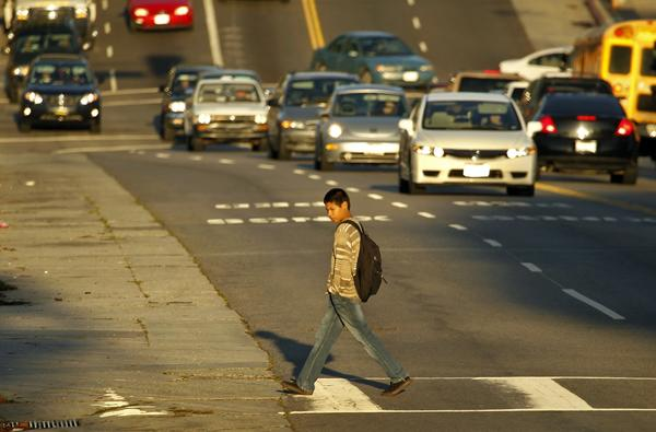 A student walks across West Temple street at Laveta Terrace in Los Angeles.