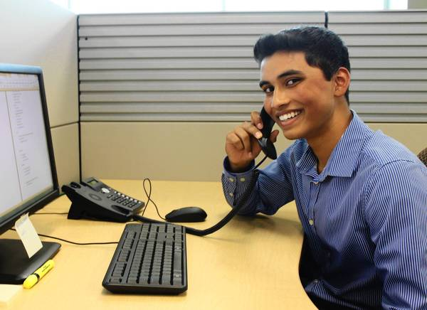 Neuqua Valley High School senior Colin Pinto works the phone for his summer internship at the Northern Illinois Food Bank.