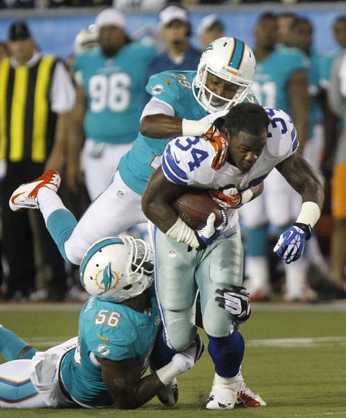 Dallas Cowboys running back Phillip Tanner (34) loses his helmet and drags Miami Dolphins cornerback Nolan Carroll and Dolphins linebacker Jonathan Freeny for first down yardage, but the ball was downed where he lost his helmet.