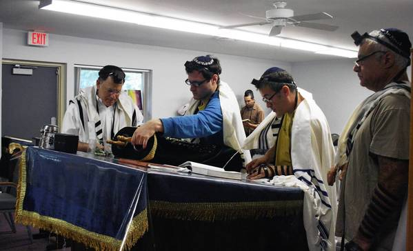 Darchei Noam of Glenbrook member Shaya Avner, center, uncovers one of congregation's two Torah scrolls during a morning service on Aug. 1. The congregation hopes to get its own synagogue in Northbrook soon.