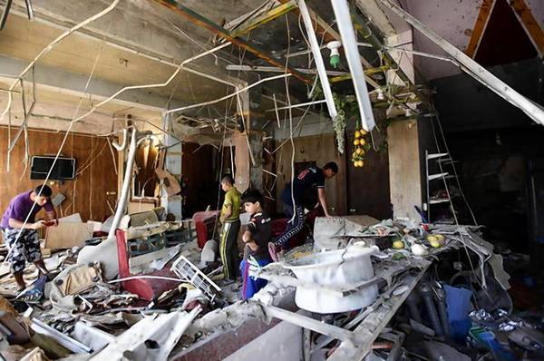 Youths survey and take pictures of the debris after a suicide bomb attack at a cafe.