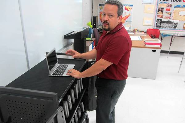 Dan Crowe, director of information technology for Mundelein Consolidated High School District 120, stands in front of a cart of Google Chromebooks that will be used for a pilot program this year. The goal is to have every student in the district with an electronic device by 2015, officials said.