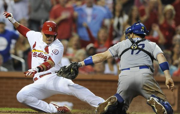 St. Louis Cardinals first baseman Craig Allen, left, is tagged out a home plate by Dodgers catcher A.J. Ellis during the fifth inning of the Dodgers' 3-2 win Monday.