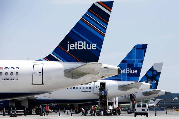 Passengers disembark from a JetBlue aircraft in Long Beach. The carrier is adding lie-flat seats in a bid for business-class passengers.