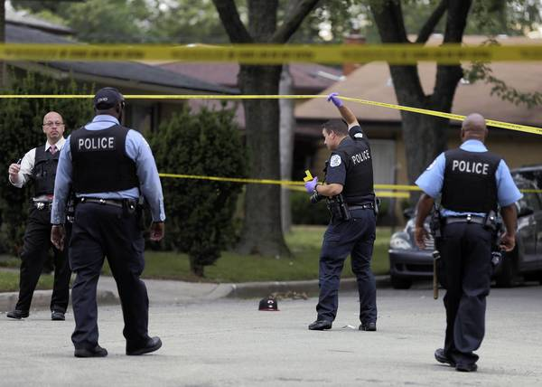 Chicago Police investigate at the scene of a shooting on 116th Street near Loomis Street in Chicago.