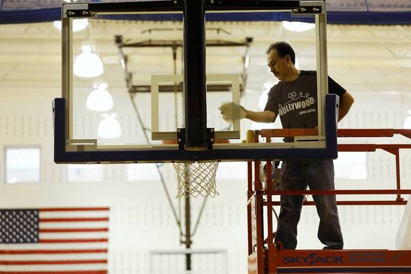 Martin Castaneda cleans a backboard at the St. Viator High School gymnasium in Arlington Heights on Monday. School officials announced this week they will begin testing students for alcohol in the fall.
