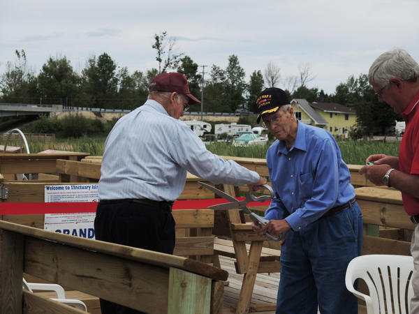 Alanson village president Richard Weidenhamer (from left) helps Derry Williams of Alanson cut the ribbon on the Sanctuary Island Park project. Williams donated the property to the village of Alanson.