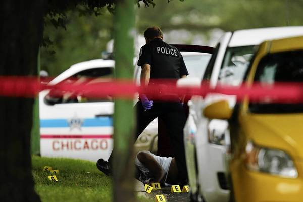 A Chicago Police officer collects evidence at the scene of a double homicide where two brothers ages 35 and 38 were killed when they were shot around 3:40 a.m. Tuesday in the 100 block of East 120th Street in Chicago.