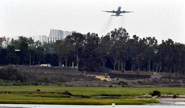 A commercial jet leaving John Wayne Airport flies over the Upper Newport Bay preserve in Newport Beach.