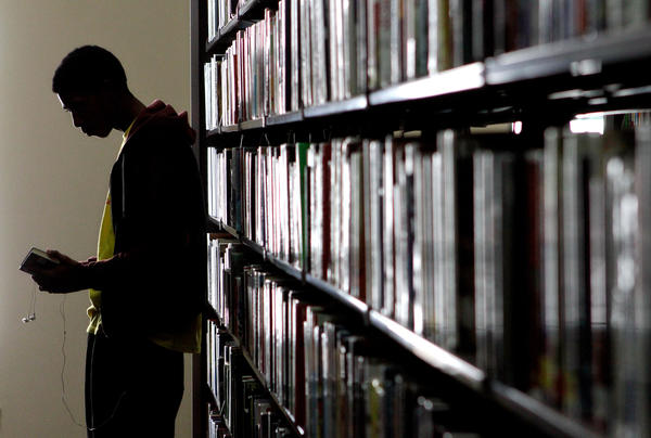 Ronny Calhoun looks for a book in the fiction stacks.