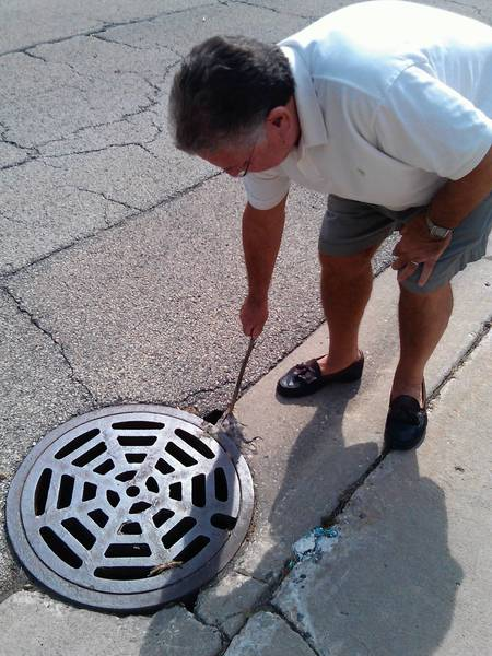 Larry Dorf, of North Avenue in Deerfield, points out a whole in the asphalt near a storm sewer at the base of his driveway. Dorf said the sewer drains don't work properly in heavy rains and had floodwater enter his home.