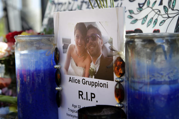 A card showing a photo of Italian newlywed Alice Gruppioni, left, and her husband, Christian Casadei, is placed at a makeshift memorial for Gruppioni along Ocean Front Walk at Venice Beach.