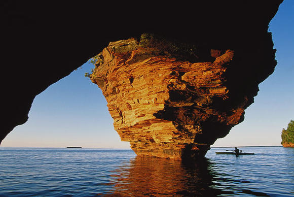 A kayaker passes a cave on Lake Superior in Wisconsin.