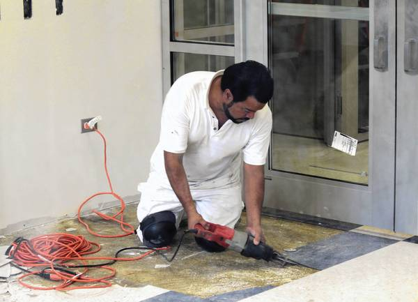 A Murphy Painting & Contracting employee takes up old vestibule flooring at the main entrance of Highland Park High School.