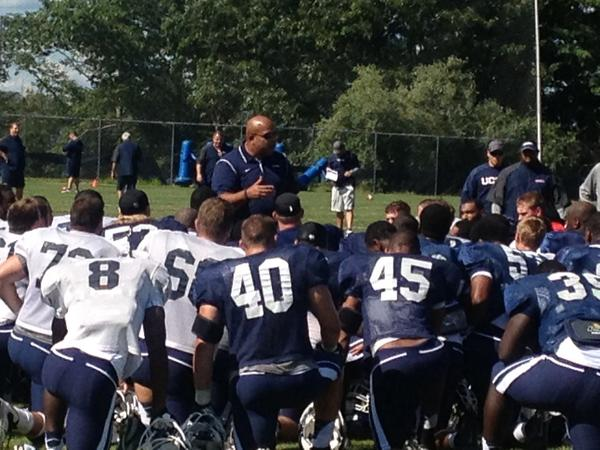 Warde Manuel speaks to UConn football players on a beautiful afternoon in Storrs.