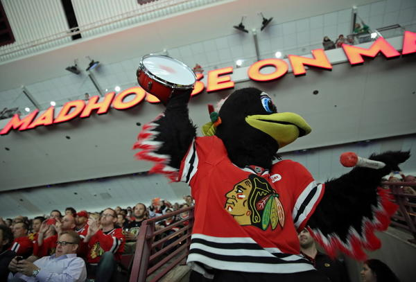 Blackhawks mascot Tommy Hawk roots with fans before Game 1 of the Stanley Cup Final at the United Center.