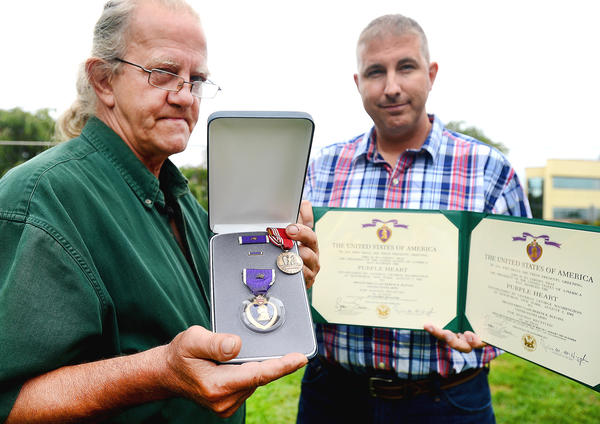 Lee Blevins, left, holds the medals presented Tuesday in honor of his late brother, Heren Blevins, who was killed in the Korean War. Army Sgt. 1st Class Lyttleton Yates, right, with the 55th Signal Co. Combat Camera Unit at Fort Meade, Md., holds both Purple Heart citations honoring Heren Blevins.