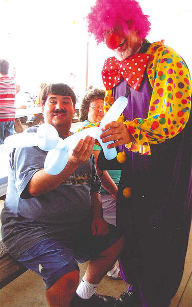 Clown Ron Kurtz hands a balloon animal he made to Kristofor Tolley at the Tri-State Civitan Club's annual picnic at The Improved Order of Red Men Tribe 84 in Williamsport.