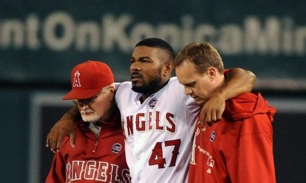 Angels second baseman Howie Kendrick, center, is helped off the field by team trainers Adam Nevala, left, and Rick Smith after suffering a knee injury during Monday's loss to the Texas Rangers.