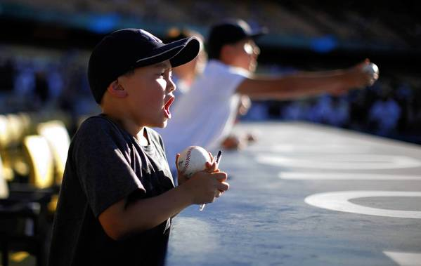 A young Yankees fan pleads with players for an autograph last month before a Yankees-Dodgers game in Los Angeles. Major League Baseball's cheaters have betrayed the religion of the game.