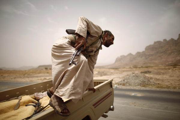 A tribal fighter jumps off a truck on a road linking the Yemeni capital Sanaa with the oil-producing province of Marib.