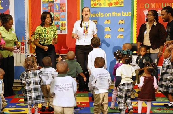 "First Lady Michelle Obama exercises with staff, parents and children at the Royal Castle Child Development Center in New Orleans in 2011 as part of her ""Let's Move!"" campaign."