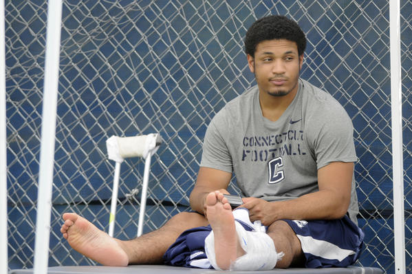 Storrs, Ct 08/06/2013 Junior Scott McCummings, out for the season with an injured Achilles' tendon, watches practice from the sidelines. The UConn football team held its second open practice for the media Tuesday at their Storrs campus. Digital Photo by Richard Messina | rmessina@courant.com