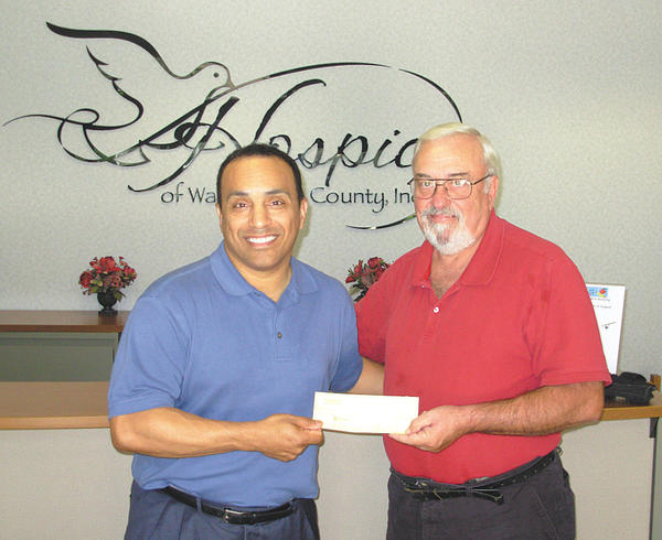 Eric Klimes, left, chief executive officer of Hospice of Washington County, and Lou Thomas, owner of the Yellow House, are shown at a check presentation in which Thomas gave Klimes a check for $2,100 for Hospice.