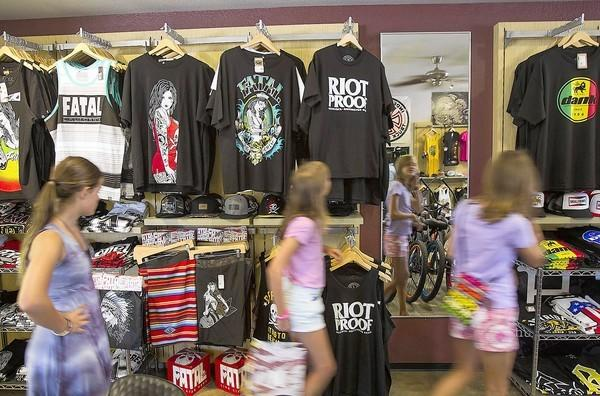 Customers drift Easyrider bike shop where t-shirts playing off the July 28th riots are being sold.