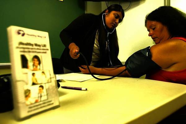 Elizabeth Ramos, a community health worker with QueensCare Health and Faith Partnership, checks the blood pressure of Anna Ovalle, 53, at La Placita Church in Los Angeles.