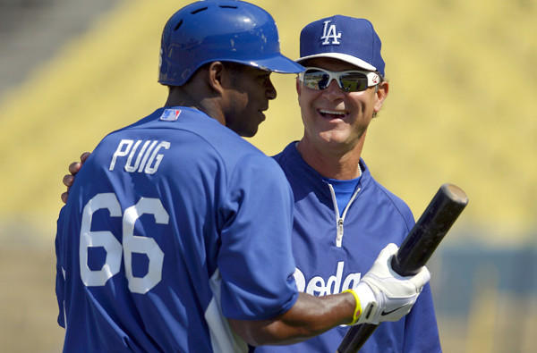 Dodgers Manager Don Mattingly talks to rookie sensation Yasiel Puig during batting practice before a game last month at Dodger Stadium.