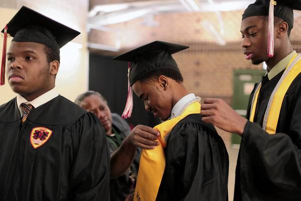 Marvin Williams, graduating from Hales Franciscan High School, gets some help with his gown while waiting for the start of the Mass Black Male Graduation Ceremony on June 29 on the grounds of Chicago State University. Hales will welcome its first female students this year.