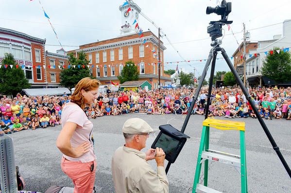 Charlotte Richardson, left, and photographer James Ivey with Central Photo Co. of Washington, D.C., took three panoramic photos Wednesday morning of the hundreds of people gathered in the square in Greencastle, Pa., for the official Old Home Week 2013 group photo.