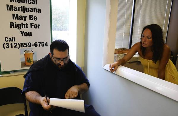 John, left, who did not want to give his last name but said he has scoliosis of the spine, receives help from Tammy Jacobi as he registers at a medical marijuana clinic Wednesday.