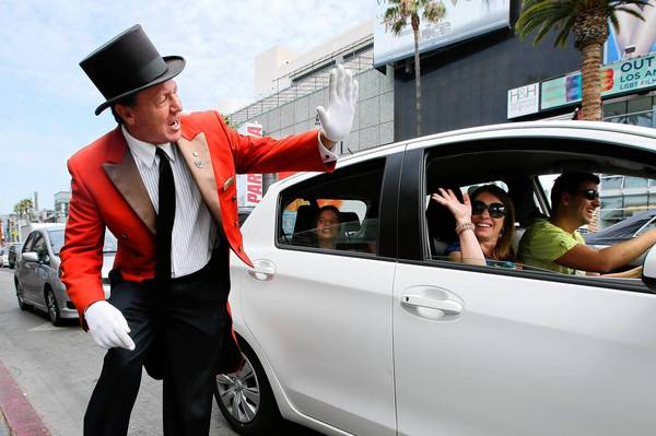 Gregg Donovan waves to passing motorists along Hollywood Boulevard.