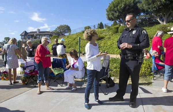 Laurie Horn, left, talks with Lt. Jay Short, with the Newport Beach Police Department, during a Spyglass Hill community picnic on Tuesday, August 6. The picnic is sponsored by the Spyglass Hill Neighborhood Watch committee.