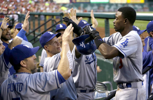 Dodgers shortstop Dee Gordon is congratulated by teammates in the dugout after scoring on single by Jerry Hairston Jr. in the second inning of a game against the St. Louis Cardinals on Wednesday.
