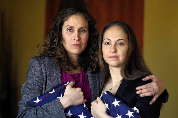 The case against Sabrina Russell, left, and Jodi Geibel — shown in March at home in Hainesville, holding flags Russell brought back from Iraq and Afghanistan — developed after another sailor found photos of them on Russell's phone.