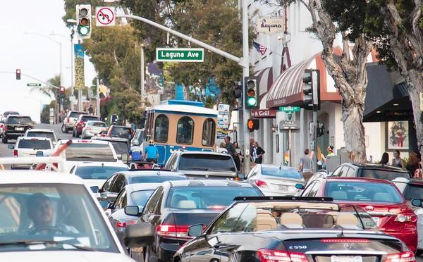 Two bicyclists wind their way by a trolley in gridlocked traffic Sunday on Coast Highway in downtown Laguna Beach.